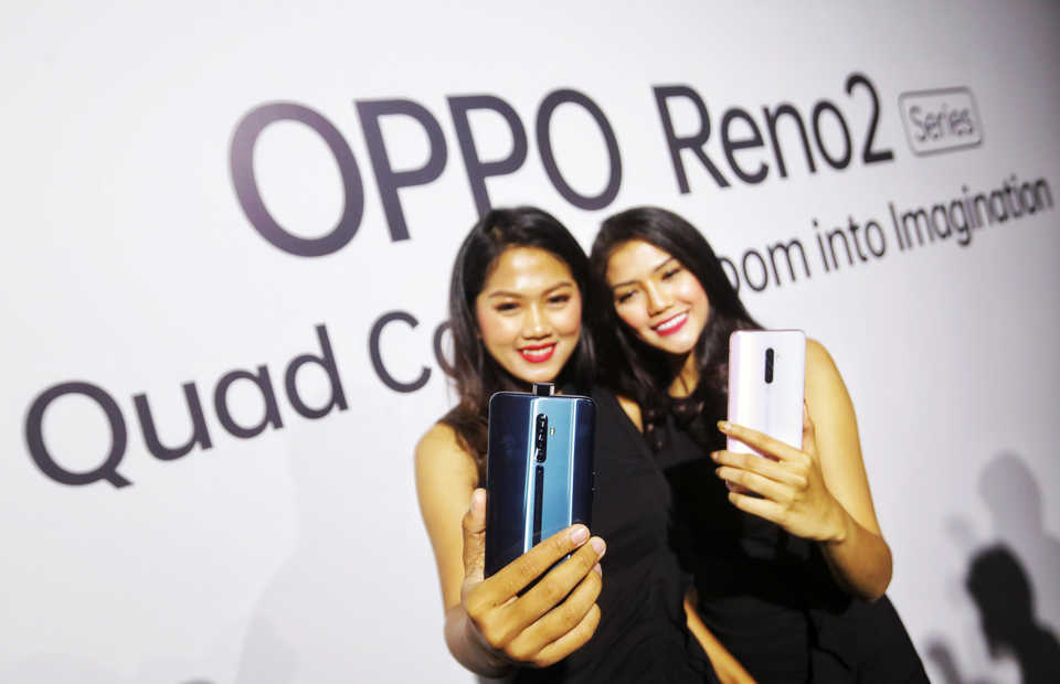 Two models show the latest Oppo smartphones during a launch event in Jakarta in October. (B1 Photo/Ruht Semiono)