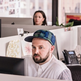 Man in blue cap working at workstation in open office