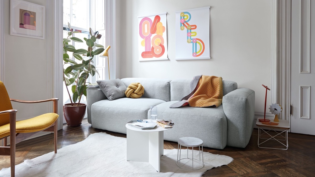 Airy living room with gray couch, yellow chair, and bright artwork on walls