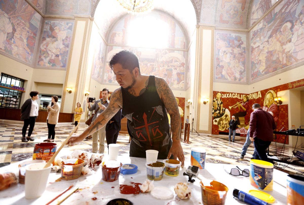 A person stands in front of a table with paints. Many murals are shown in the background.