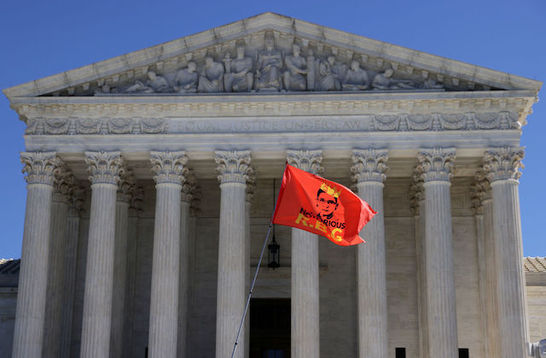 The Supreme Court stands in the background as a red flag with a drawing of Justice Ruth Bader Ginsberg and the words Notorious RBG flies in the foreground.