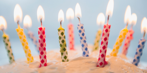 Colorful candles lit on a cake - Hero Image