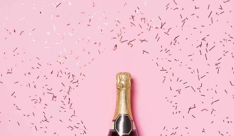 A picture of a champgne bottle and gold confetti