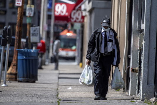 A Black man wearing a security guard uniform and a mask due to coronavirus concerns walks down a desolate New York street