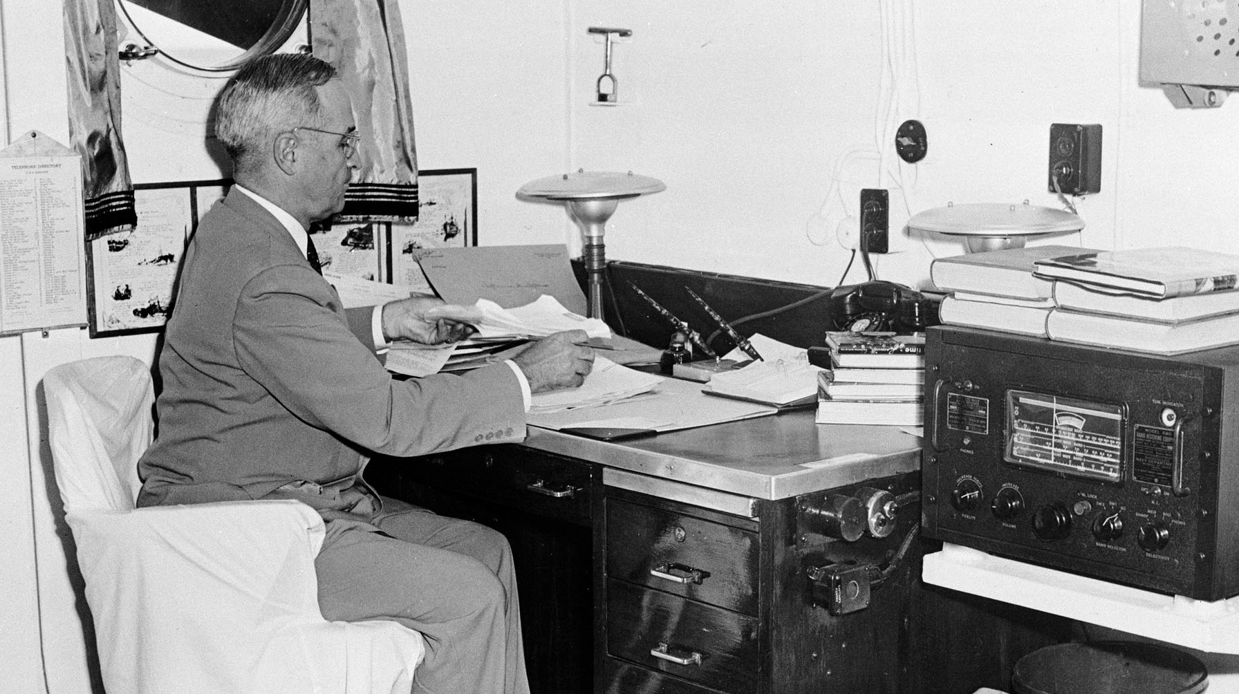 President Harry S. Truman, with a radio at hand, reads reports of the first atomic bomb raid on Japan, while en route home from the Potsdam conference, August 6, 1945. (AP Photo)