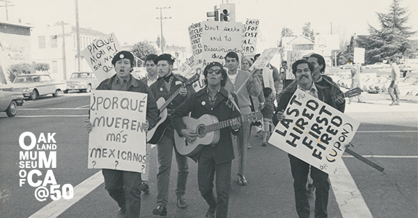 Black and white image of a large group of people with protest signs marching down a street