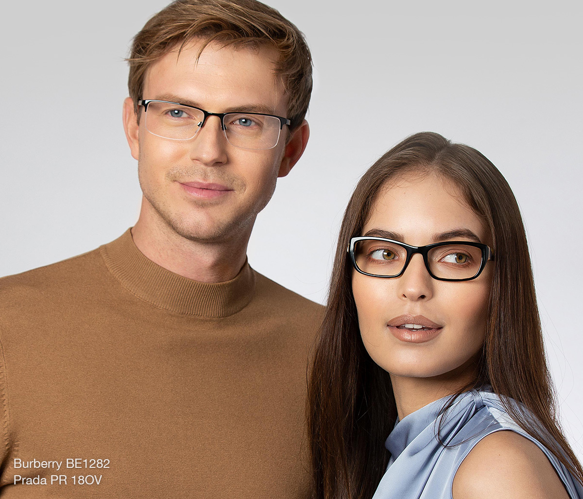 A man with light brown hair wearing a brown sweater and Burberry BE1282 glasses standing next to a brunette woman wearing a light blue top and Prada PR 18OV glasses