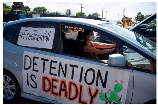 """Protest against Detention. Woman in car with two signs reading """"Detention is Deadly"""" and """"Free Them All"""""""