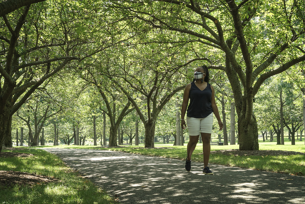 Woman in mask walking through garden