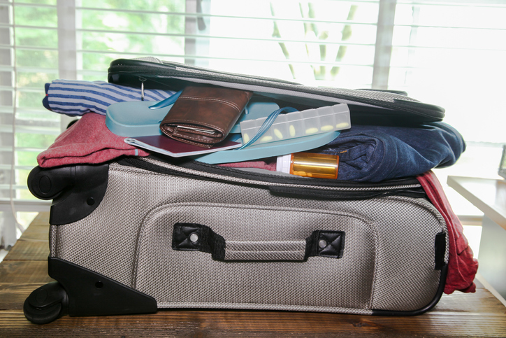 Full suitcase packed for vacation including medications