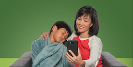 Woman woman using a tablet while comforting her son - image