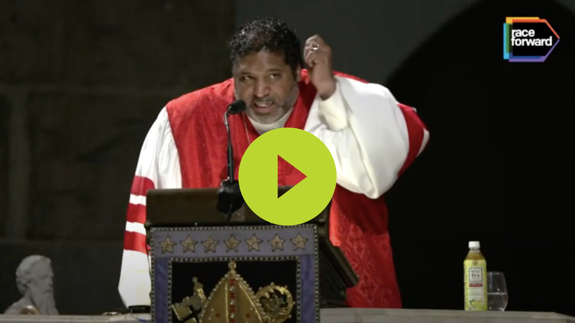 """Image of Rev Barber in robes speaking passionately to an audience, with a lime green """"play"""" button in the center of the image. Click to watch the Rev. Dr. Barber announcement video!"""