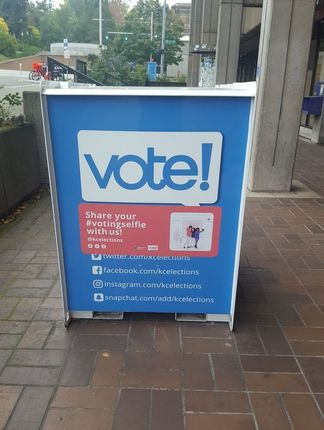 A blue King County voting drop-off box on brick sidewalk in Seattle