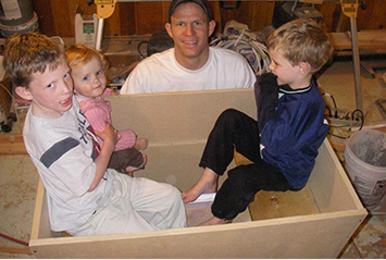 The kids sitting in the first bucket made of wood planks