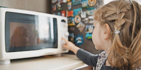 Young girl turns on microwave - Hero Image