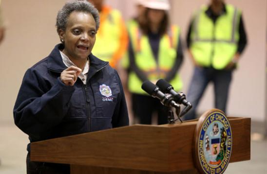 Chicago Mayor Lori Lightfoot. Brown-skinned Black woman with short salt and pepper hair, dressed in a blue windbreaker jacket