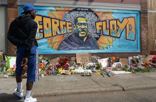 George Floyd. A man stands in front of a George Floyd mural in South Minneapolis.