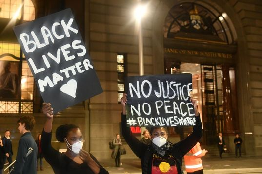 """Two young black women holding """"Black Lives Matter"""" and """"No Justice, No Peace"""" wearing black shirts and masks."""