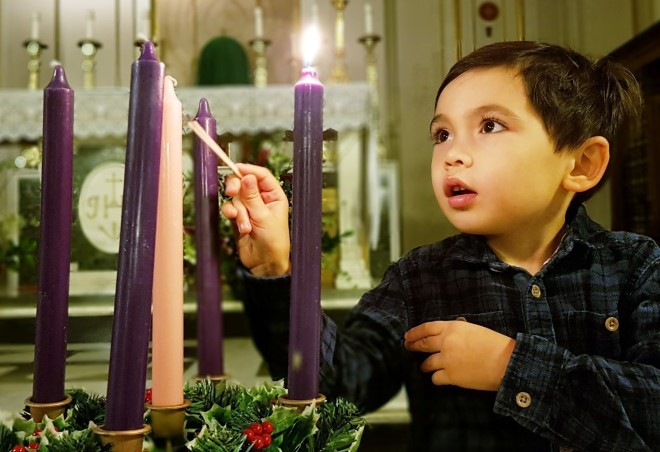 A child lights an Advent candle.