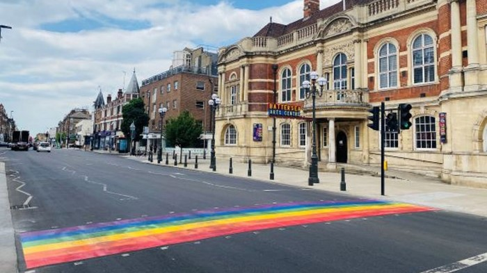 A rainbow road crossing leads to a large Victorian building. A sign ''Battersea Arts Centre'' is visible.