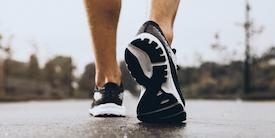 Feet wearing black sneakers walking on pavement - image