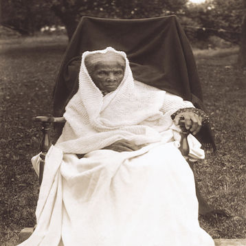 Harriet Tubman is sitting on a chair outside of her home in New York in 1911.