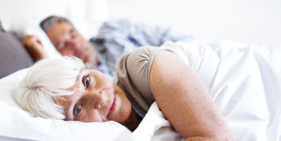 Couple in bed, older woman looks at camera - image