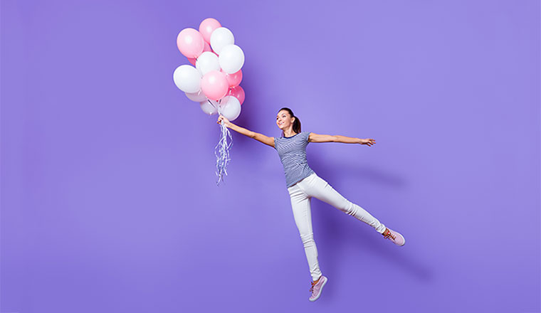 A photo of an engaged staff member being carried away by balloons