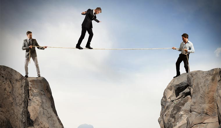 A picture of an agent walking across a rope supported by colleagues