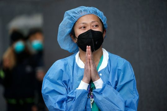 Asian Nurse with blue scrubs and head covering and black mask with hands clasped together in front of her in prayer position.