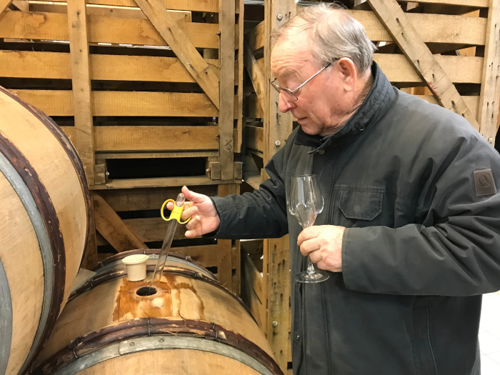 image of Diebolt sampling wine from a barrel, holding a wine glass