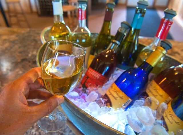 A glass of white wine with bottles in background