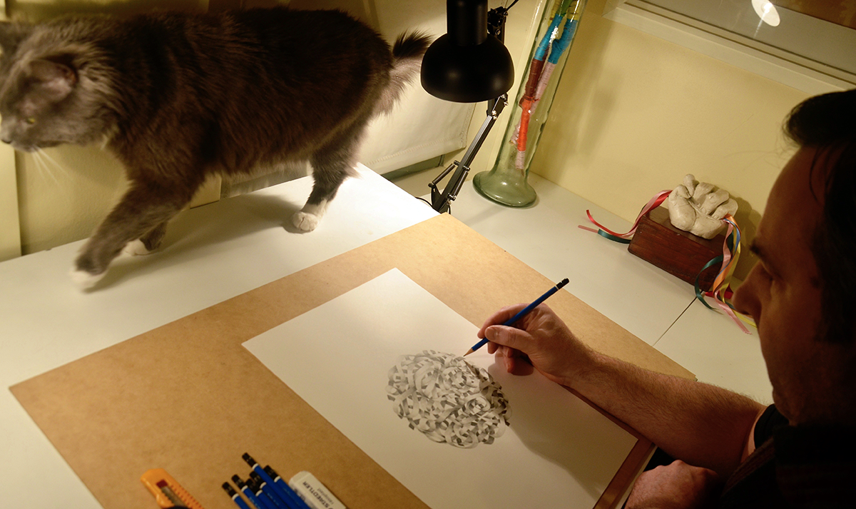 Adam Knapper sketching a pencil drawing with ribbons interlocked in the shape of a ball.