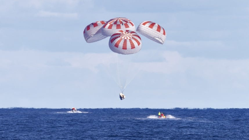 A SpaceX Crew Dragon spacecraft descends under its