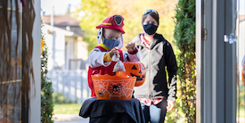 Toddler in costume and mask grabs treat bag from bucket - image