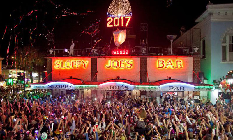 Main banner image depicts a large party taking take in New Years Eve outside a Sloppy Joe Restaurant