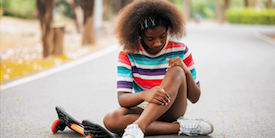 Tween aged girl holding her leg on the ground - Image