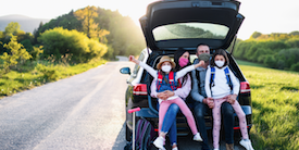 Family with young child pose behind their car - Hero Image