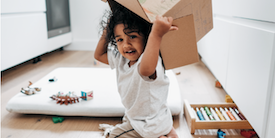 Toddler boy with a box on his head - image