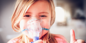 Young girl using a nebulizer giving thumb up sign - image