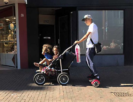 dad pushes double stroller while on hoverboard
