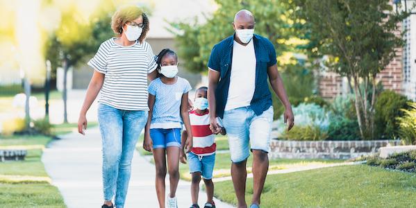 Family wearing masks walking outside - image