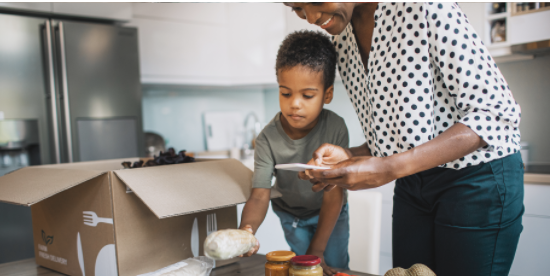 Mother and son unpack groceries and read labels - Hero Image