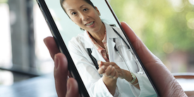 Hand holing smart phone with image of doctor inthe screen - image