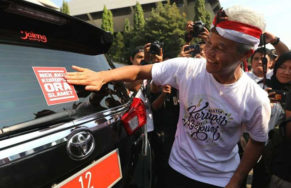 Central Java Governor Ganjar Pranowo stick a sticker on a government car that carries an oath to never commit corruption in Semarang on Sunday.(Photo courtesy of Central Java government)
