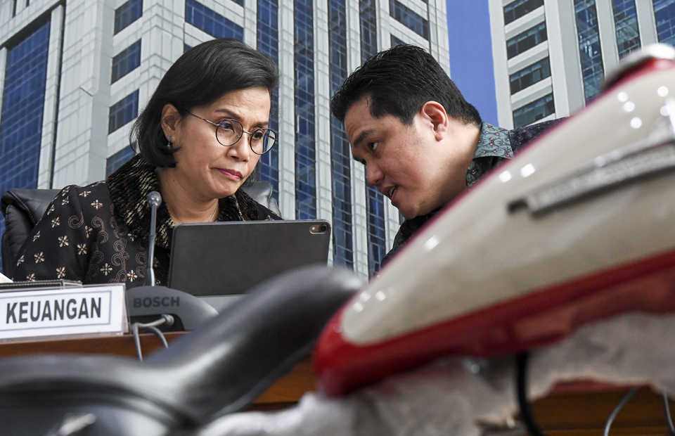 Finance Minister Sri Mulyani, left, chats with State-owned Enterprises Minister Erick Thohir during a press conference discussing alleged smuggling of a Harley Davidson motorcycle and two foreign bicycles in Jakarta on Thursday. (Antara Photo/Hafidz Mubarak)