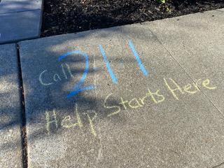 chalk words on sidewalk saying call 211 Help starts here