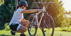 Woman checks her bike tire - image