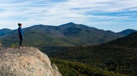 A woman looks out at mountains with hints of fall foliage