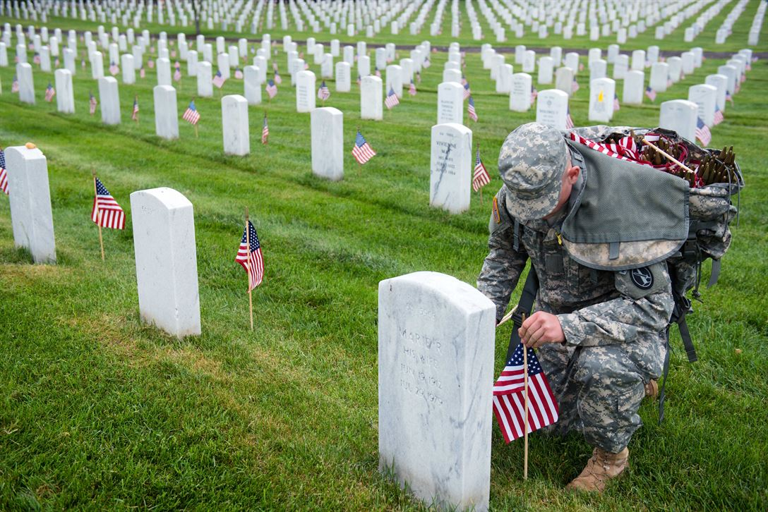 Soldier puts a flag down in Arlington Cemetery in Virginia.